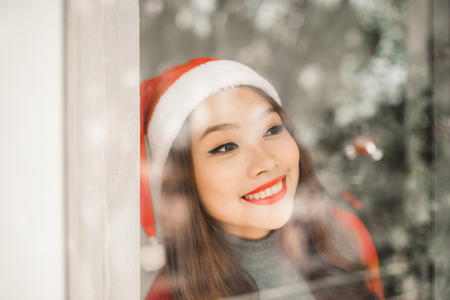 Happy young asian woman  near christmas tree celebrating New Year