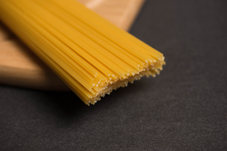 Dry spaghetti pasta tied up with rope on dark stone table