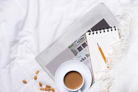 朝のコーヒーと布トップ ビュー女性創造的なビジネス概念に木製の鉛筆と日記