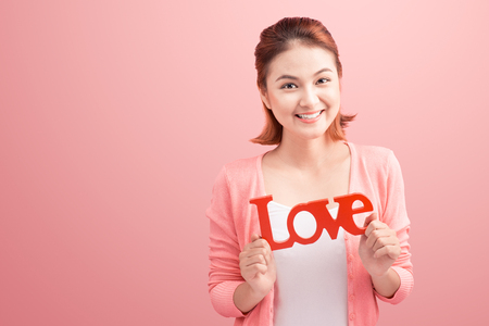 Pretty asian young woman holding wooden letters LOVE on link background.