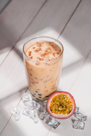 Bubble tea. Homemade Passion Fruit Milk Tea with Pearls on wooden table.