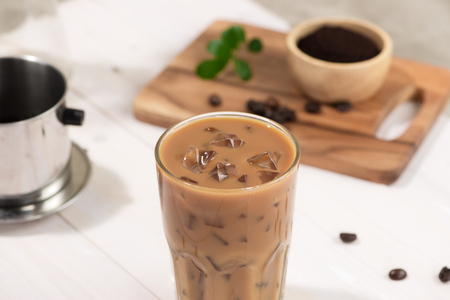 Ice coffee with fresh coffee on a wooden background, Coffee with milk and ice on natural wooden