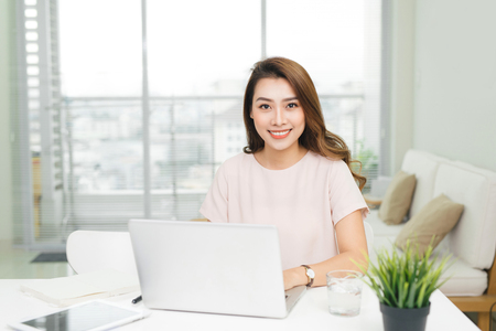 Attractive businesswoman working on laptop and smiling for camera in workplace Stok Fotoğraf