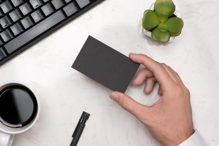 Mockup of black business cards in mans hand