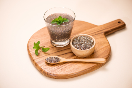 Selective focus of chia seeds drink with water in transparent glass with lemon balm.