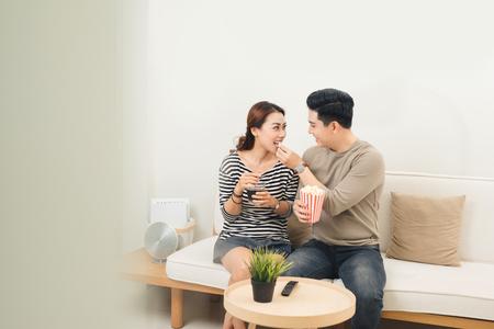 Glückliche asiatische Familie, die zu Hause Popcorn isst Standard-Bild