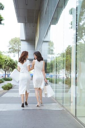 belles jeunes femmes heureuses avec des sacs sur la rue au centre commercial