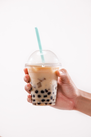 Hand holding light brown creamy bubble tea and black tapioca pearls in plastic cups on table. Stock Photo - 88199540