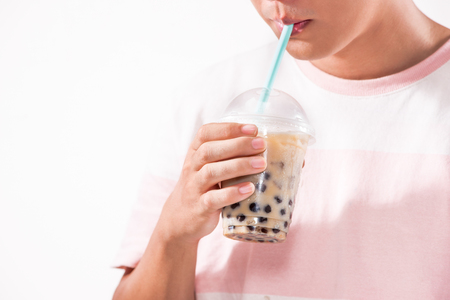 Drinking light brown creamy bubble tea and black tapioca pearls in plastic cups on table. Stock Photo - 88199549