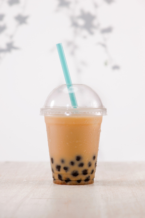 Light brown creamy bubble tea and black tapioca pearls  in plastic cups on table. Stock Photo - 88199504