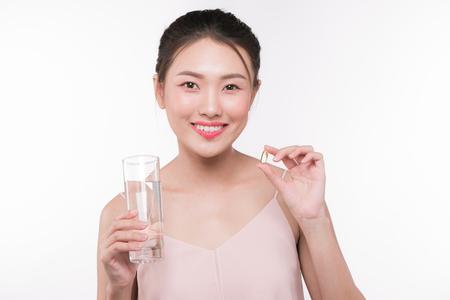 Glimlachende Aziatische vrouw die pillen en drinkwater eet Stockfoto