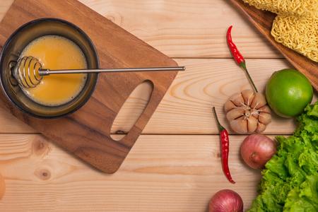 Instant-Nudeln zum Kochen und essen in den Teller mit Rührei und Gemüse auf Holzuntergrund Standard-Bild - 88488189