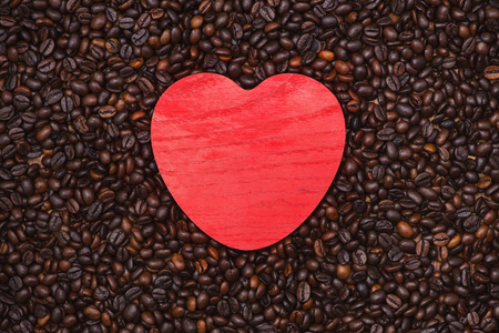Red wooden heart shape on coffee beans background.