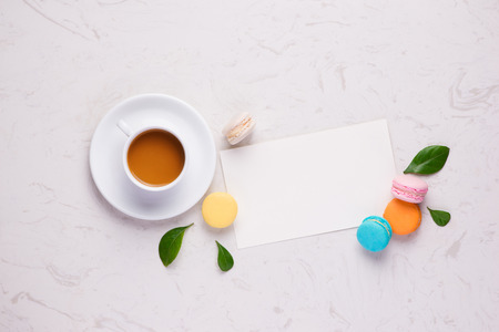 Colorful flat lay with flowers macaroons and cup of tea. Spring concept.