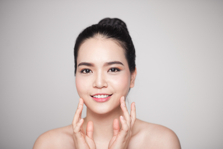Happy smiling beautiful asian woman touching her face. Stock Photo - 88488629