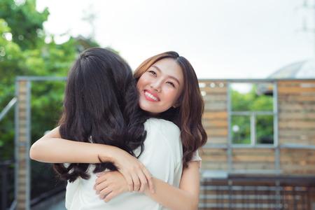 Aziatische zusters die en in het park koesteren glimlachen.
