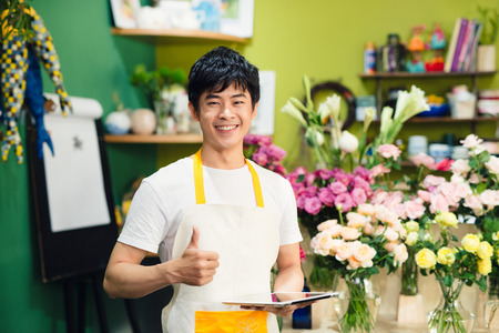 Cropped image of asian male florist making notes at flower shop counter Stok Fotoğraf