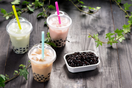 Variety of bubble tea in plastic cups with straws on a wooden table. Stock Photo