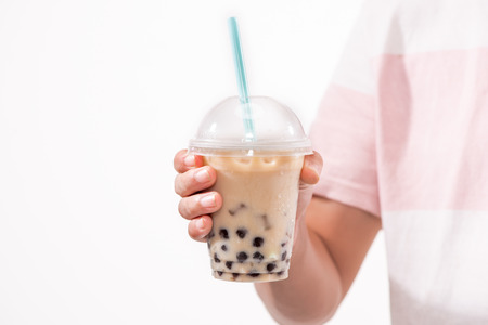 Drinking light brown creamy bubble tea and black tapioca pearls in plastic cups on table.