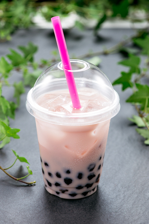 Bubble boba tea with milk and tapioca pearls in plastic cup