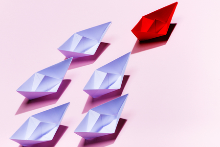 Leadership concept. Red paper ship leading among white Stock Photo