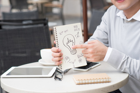 Cheerful asian businessman showing creative idea documents