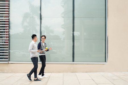 Two asian men talk and use smart phone outside the building Stok Fotoğraf