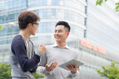 Salesman trying to sell products to a client showing them in a tablet outdoors