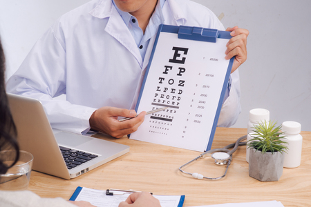 Male doctor pointing at the letters on the eye chart for her patient to read Standard-Bild