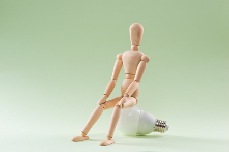 Wood figure mannequin sitting on an incandescent light bulb