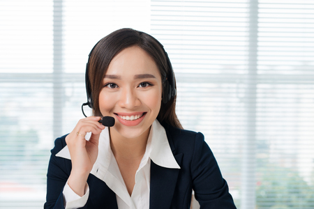 Call center operators. Young beautiful asian business woman in headset. Stock fotó