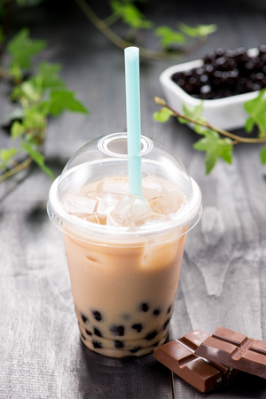 Homemade chocolate milk bubble tea in plastic cups on table.