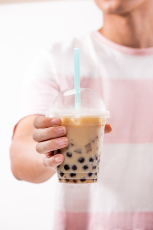 Hand holding light brown creamy bubble tea and black tapioca pearls in plastic cups on table. Stock Photo