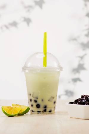 Lemon bubble boba tea with milk and tapioca pearls in plastic cup