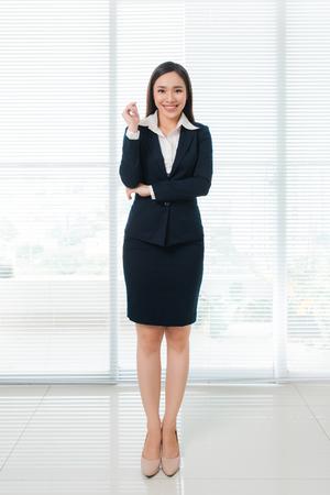 사무실에서 서있는 동안 카메라를 찾고 자신감 아름 다운 젊은 아시아 여자의 전체 길이.