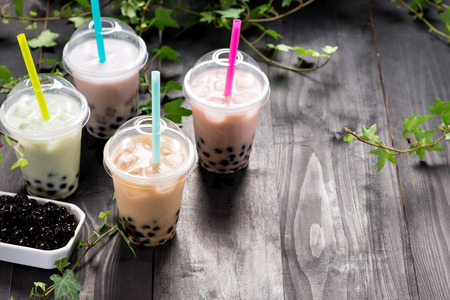 Variety of bubble tea in plastic cups with straws on a wooden table. Stock Photo - 88830189