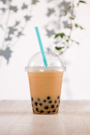 Homemade milk bubble tea in plastic cups on table. Stock Photo - 88960789