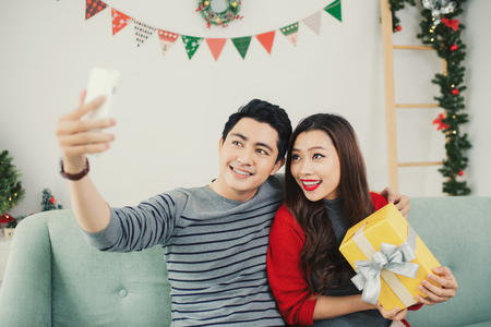 Christmas Asian Couple. A handsome man giving her girlfriendwife a gift at home celebrating New Year People Stock Photo