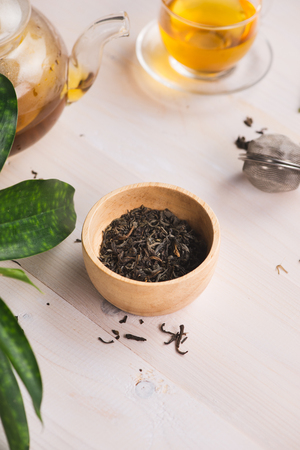 Dry tea in bowl, on wooden background