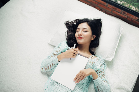 Author, Typewriter, Journalist. Intelligent woman lying on bed and thinking