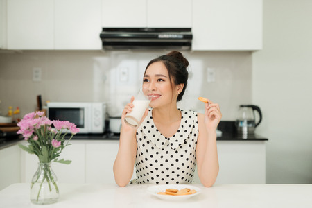 Young asian woman holding milk glass bite cookie in her kitchen