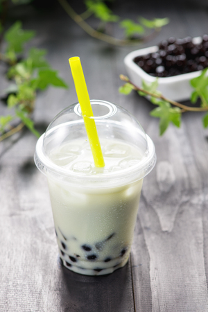 Homemade milk bubble tea in plastic cups on table.