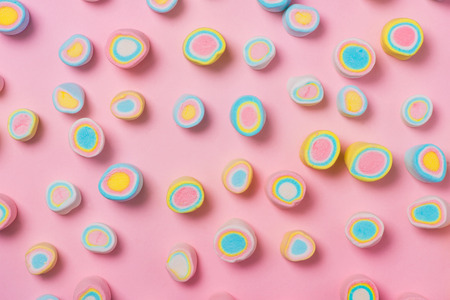 Minimal flat lay. Top view of the pastel marshmallows on a pinkbackground.  Stock Photo
