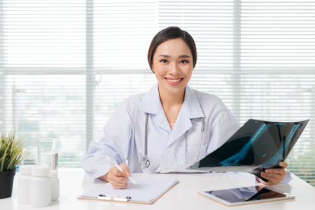 Beautiful asian female doctor examining Xray report in clinic 스톡 콘텐츠