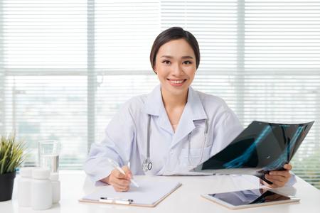 Beautiful asian female doctor examining Xray report in clinic Foto de archivo