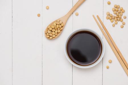 Sojasaus en sojaboon met eetstokjes op houten lijst