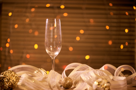 A glass with champagne and golden Christmas balls Stok Fotoğraf