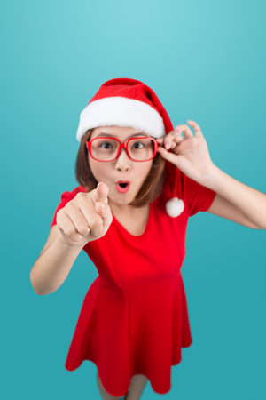Full-body of attractive cheerful asian girl in Santas hat pointing with her hand at copy space and happy smiling