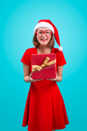 Mrs. Santa. Beautiful young asian woman in santas hat holding a gift isolated on blue. Stock Photo