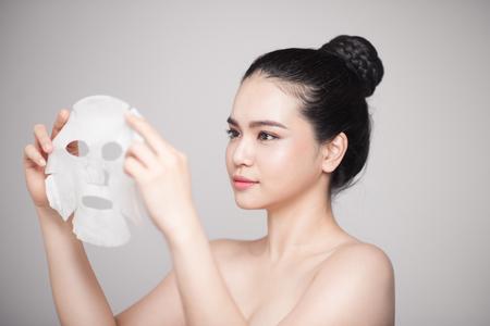 スパ、ヘルスケア。白い背景に孤立した彼女の顔に浄化マスクを持つ女性